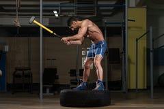Entrenamiento en el gimnasio con el neumático del martillo y del tractor Imagenes de archivo