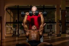 Entrenamiento en el gimnasio donde el socio da el estímulo Fotos de archivo