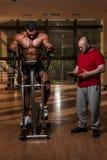 Entrenamiento en el gimnasio donde el socio da el estímulo Foto de archivo libre de regalías