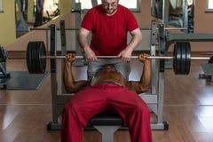 Entrenamiento en el gimnasio donde el socio da el estímulo Fotografía de archivo