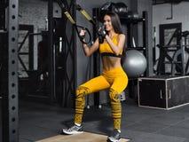 Entrenamiento en la gimnasia Muchacha de la aptitud para acumular los músculos con TRX Imágenes de archivo libres de regalías