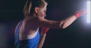 Entrenamiento femenino del boxeador en sitio oscuro con el contraluz en vista lateral de la c?mara lenta tiro del steadicam metrajes