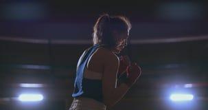 Entrenamiento femenino del boxeador en sitio oscuro con la luz trasera en la c?mara lenta tiro del steadicam almacen de video