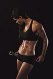 Entrenamiento femenino muscular del levantamiento de pesas que hace Imágenes de archivo libres de regalías