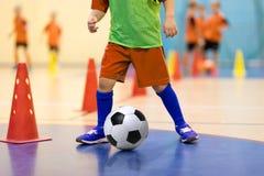 Entrenamiento futsal del fútbol para los niños Taladro de goteo del cono del entrenamiento del fútbol Jugador de los jóvenes del  Imagen de archivo libre de regalías