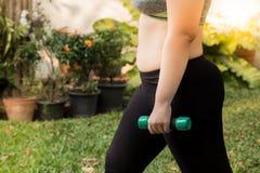 Entrenamiento gordo del ejercicio de la pérdida de peso de la mujer con pesa de gimnasia de la elevación en el jardín Imagen de archivo