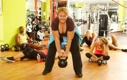 Entrenamiento gordo resuelto de la mujer en club de salud Foto de archivo