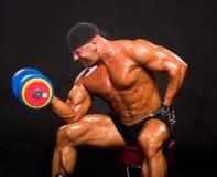 Entrenamiento hermoso del culturista con pesa de gimnasia pesada Imagen de archivo libre de regalías