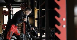 Entrenamiento hermoso del hombre de la aptitud con pesas de gimnasia en gimnasio almacen de metraje de vídeo
