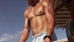 Entrenamiento hermoso dinámico atractivo joven del hombre con el Barbell en una playa metrajes