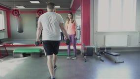 Entrenamiento individual con el coche de la muchacha para el hombre en gimnasio El individuo obeso grueso con el instructor priva almacen de video