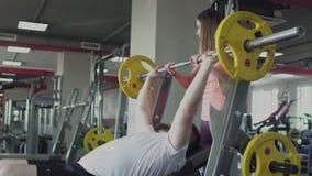 Entrenamiento individual con el coche de la muchacha para el hombre en gimnasio Individuo obeso grueso con el instructor privado  almacen de metraje de vídeo