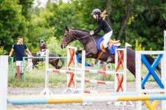 Entrenamiento joven de la muchacha del jinete que salta con su instructor Fotografía de archivo