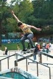 Entrenamiento joven del skater en el parque del patín en la verja Fotografía de archivo libre de regalías