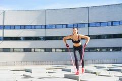 Entrenamiento joven y deportivo de la muchacha con la banda elástica al aire libre Fotos de archivo