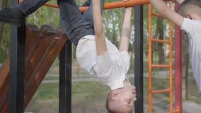 Entrenamiento juguetón de dos hermanos de gemelos y el jugar en las barras horizontales en el patio en parque de la primavera metrajes