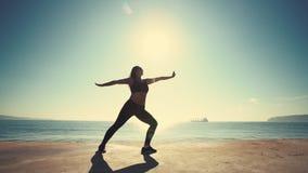 Entrenamiento juguetón hermoso de la muchacha en la salida del sol sobre la playa Mujer que hace yoga contra el mar y el sol almacen de video