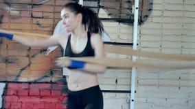 Entrenamiento kickboxing hermoso de la mujer que perfora con la goma en kickboxer apto del cuerpo de la fuerza feroz del estudio  metrajes