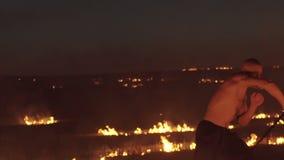 Entrenamiento libre del combatiente con la espada en el campo ardiente de la noche lentamente almacen de metraje de vídeo