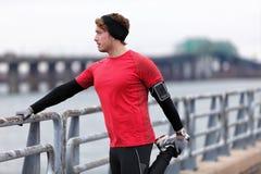 Entrenamiento masculino del corredor en el invierno frío que hace calentamiento Foto de archivo libre de regalías