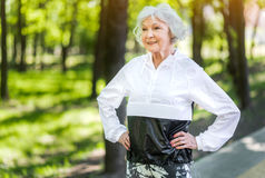 Entrenamiento mayor alegre de la señora entre árboles verdes fotos de archivo