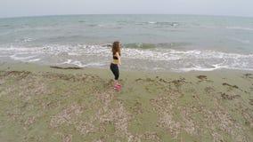 Entrenamiento moreno del atleta de sexo femenino en la playa arenosa, haciendo posiciones en cuclillas, deporte y salud almacen de metraje de vídeo