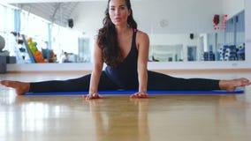 Entrenamiento moreno joven que su flexibilidad en cruz partió en la estera en el gimnasio metrajes