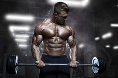 Entrenamiento muscular atlético brutal del culturista con el barbell en el gimnasio Imagen de archivo libre de regalías