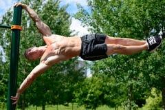 Entrenamiento muscular de la calle de la práctica del hombre en un gimnasio al aire libre Fotografía de archivo