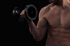 Entrenamiento muscular del hombre con pesa de gimnasia Imagen de archivo libre de regalías