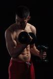 Entrenamiento muscular del hombre con pesas de gimnasia Imágenes de archivo libres de regalías