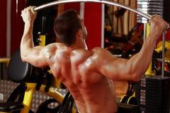 Entrenamiento muscular del hombre en gimnasio Imagenes de archivo