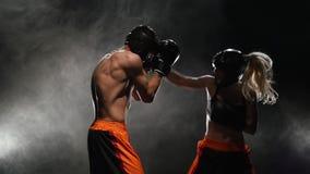 Entrenamiento para kickboxing del soplo él se cae al piso Fume el fondo Cámara lenta metrajes