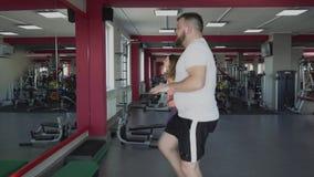 Entrenamiento personal con el instructor de la muchacha para el hombre con el abdomen grande en gimnasio El individuo obeso grues almacen de metraje de vídeo