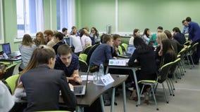 Entrenamiento práctico de estudiantes en los ordenadores portátiles en la lección de la economía Los estudiantes teambuilding par almacen de metraje de vídeo