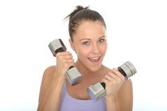 Entrenamiento resuelto feliz sano de la mujer joven del ajuste con los pesos mudos de Bell Imagen de archivo