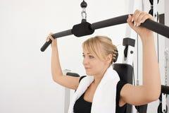 Entrenamiento rubio joven de la mujer en gimnasia Fotografía de archivo libre de regalías