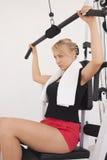 Entrenamiento rubio joven de la mujer en gimnasia Foto de archivo libre de regalías