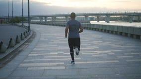 Entrenamiento sano joven del hombre negro y construcción de su cuerpo que hace fithness y ejercicio en la acera en la cámara lent almacen de metraje de vídeo