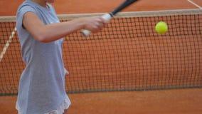 Entrenamiento sonriente joven de la muchacha en el campo de tenis almacen de video