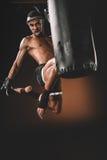 Entrenamiento tailandés con el saco de arena, concepto del combatiente de Muay del deporte de la acción Imagen de archivo libre de regalías