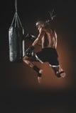 Entrenamiento tailandés con el saco de arena, concepto del combatiente de Muay del deporte de la acción Imagen de archivo