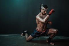 Entrenamiento tailandés del atleta de Muay en el encajonamiento tailandés dentro Fotografía de archivo libre de regalías