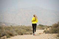 Entrenamiento trasero de la muchacha del corredor del deporte de la visión en paisaje sucio de la montaña del desierto del camino Foto de archivo libre de regalías