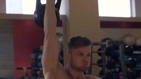 Entrenamiento whileodybuilding de elevación del peso del hombre fuerte del retrato en primer del club del gimnasio metrajes