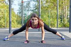 Entrenamientos caucásicos jovenes de la mujer en el sportsground del parque Fuerza activa y el estirar, ropa de deportes brillant foto de archivo