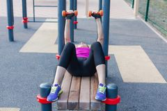 Entrenamientos caucásicos jovenes de la mujer en la tierra de deportes del parque con las pesas de gimnasia, poniendo en la barra imagenes de archivo
