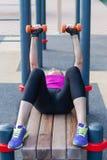 Entrenamientos caucásicos jovenes de la mujer en la tierra de deportes del parque con las pesas de gimnasia, poniendo en la barra fotografía de archivo