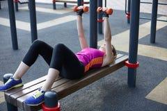 Entrenamientos caucásicos jovenes de la mujer en la tierra de deportes del parque con las pesas de gimnasia, poniendo en la barra foto de archivo