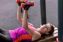 Entrenamientos caucásicos jovenes de la mujer en la tierra de deportes del parque con las pesas de gimnasia, poniendo en la barra fotos de archivo